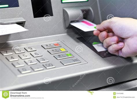 mon you bank inserting atm credit card into bank machine to