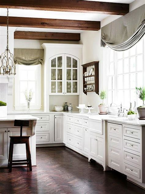 white kitchen cabinets with gothic arch glass front doors herringbone pattern wood floors and dark wood ceiling