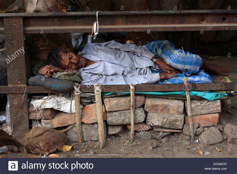 makeshift bed homeless indian man asleep beside the street in a