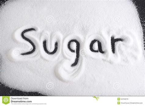 up letter with sugar word written with finger on pile of sugar in diet sweet