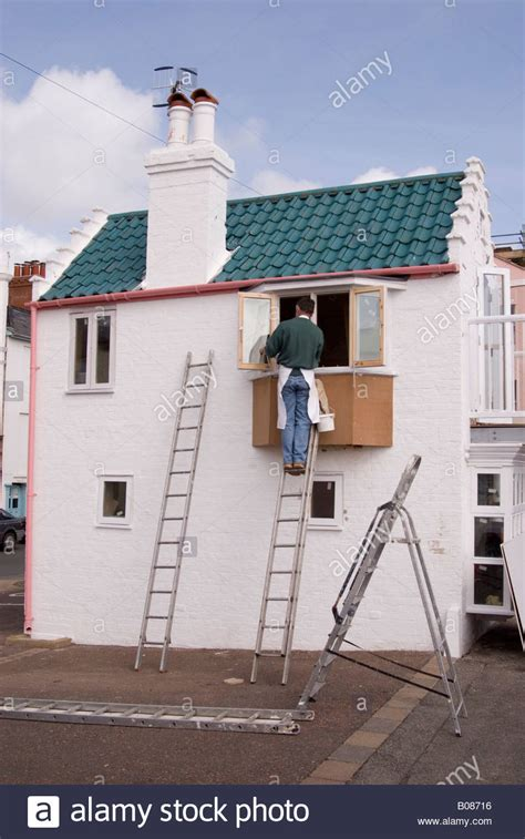 looking for a man who paints houses man painting exterior window on house up ladder in the uk
