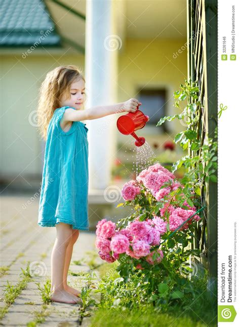 girl watering flowers cute little girl watering flowers stock photo image