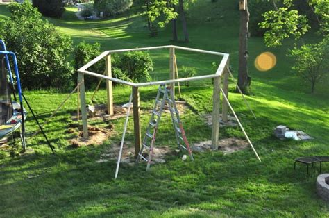 fire pit surrounded by swings he drives 6 posts into the ground in his backyard for one