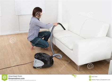 Young Woman Vacuuming Sofa At Home Stock Photo Image
