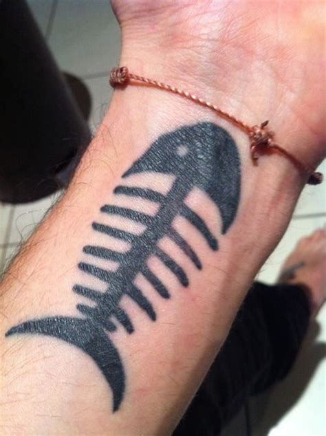 tattoo on wrist facing in or out simple fish bones on wrist simple fish design in all black