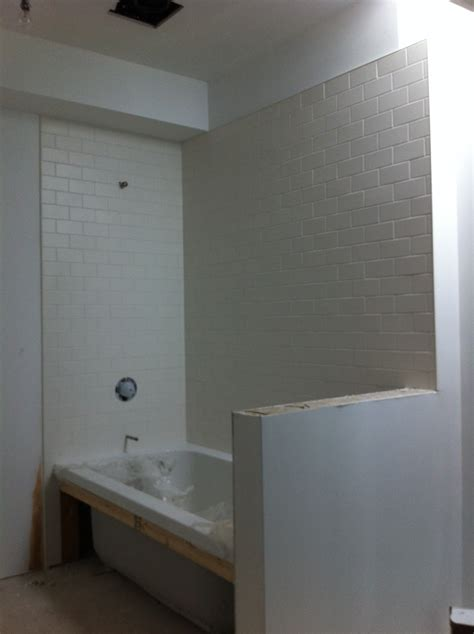 bathroom surrounds subway tile with a white hexagon floor and dark border
