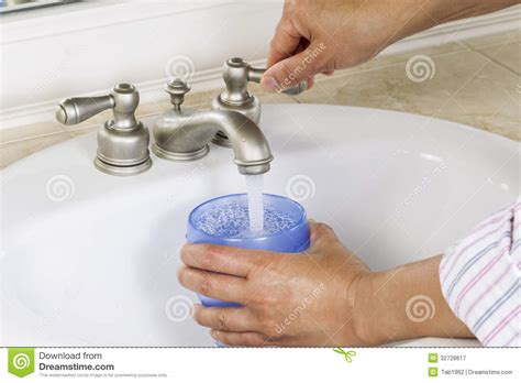drinking water from bathroom sink pouring water into cup from bathroom sink royalty free