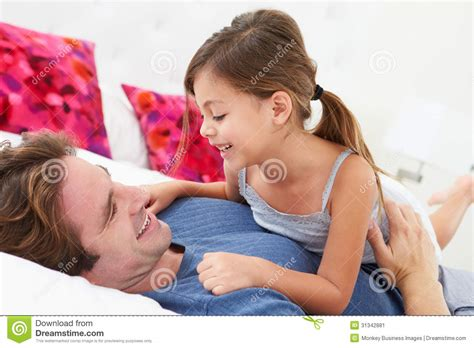 in daddys bed father and daughter lying in bed together stock image