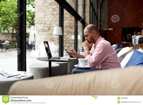 sofa shops reading male student reading message on phone sitting at sofa of