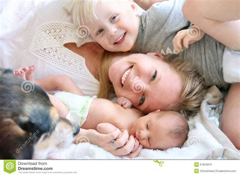 in bed with mom happy mother laying in bed with toddler son and newborn
