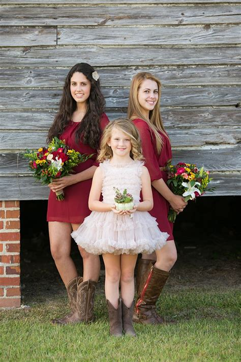 bridesmaids in deep read dresses and flower in blush