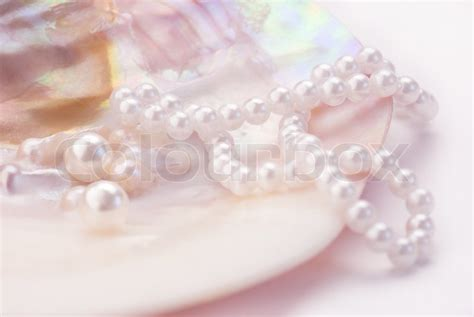 tinted image macro of pearls and necklace in an oyster shell pink