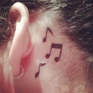 Music note tattoo behind the ear for girl