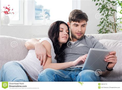couch couple couple sitting on a couch with tablet computers stock