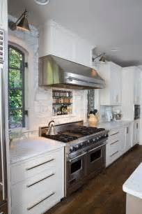 small white kitchen with steel hood stainless steel range hood with pot rail transitional