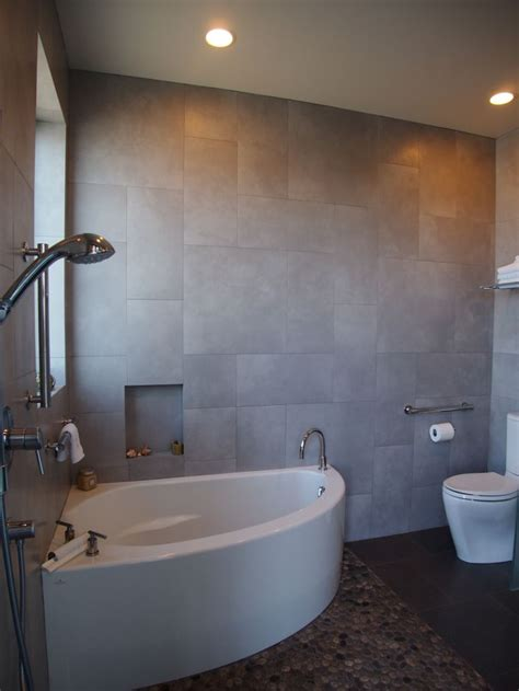 a small corner soaking tub shares a compact room with