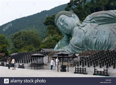giant reclining buddha worshipers praying before a giant reclining buddha statue