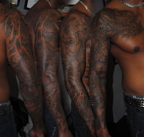 colored tattoos on dark skin blossom sleeve tatting