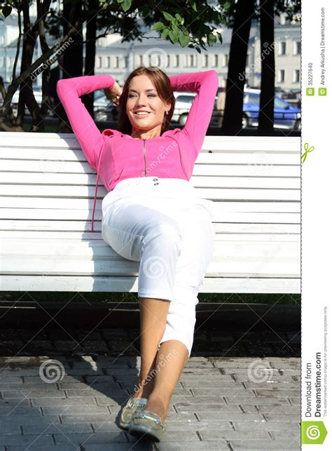 women bench young woman sitting on a park bench stock photo image