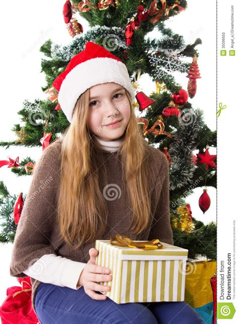 teenage girl in santa hat with present under christmas