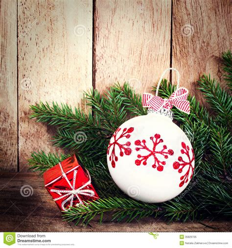 christmas ornaments with fir tree branch over wood wall
