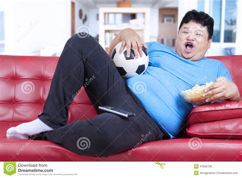 lazy on couch fat mant watching soccer match on tv stock photo image