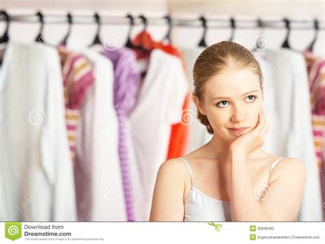 chooses clothes in the wardrobe closet at home stock