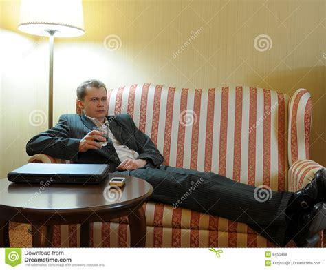 having on the sofa man having drink on sofa royalty free stock photos image