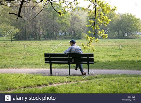 sitting in a park bench man sitting alone on park bench stock photo royalty free