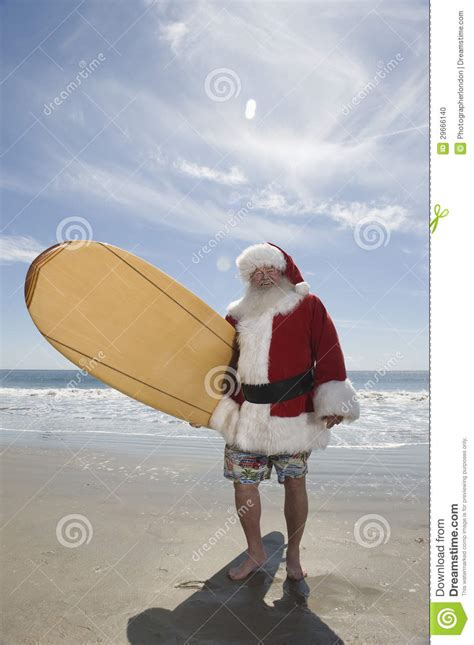 santa claus holding surfboard on beach stock photo image