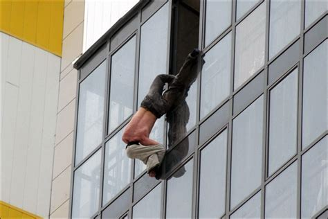 hang pictures rescue for man hanging perilously by one leg out of 15th