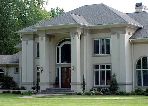 house with columns dramatic exterior with flattened columns and white stucco