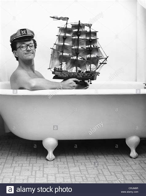 man in a bathtub man in captain hat holding toy ship in bathtub stock photo