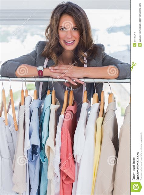 z design clothes smiling fashion designer leaning on clothes royalty free