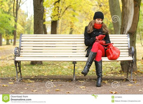 waiting on a bench a young woman waiting on the bench in the park stock photo