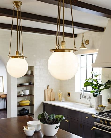 old world brass globe pendants and black kitchen cabinets