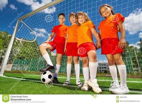 woodwork in football children with football in a row near woodwork stock photo