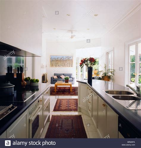 galley kitchen open to living room rugs on floor in open plan white galley kitchen with black worktops stock photo royalty free