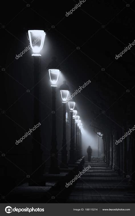 persona illuminata persona cammina sulla strada buia illuminata con