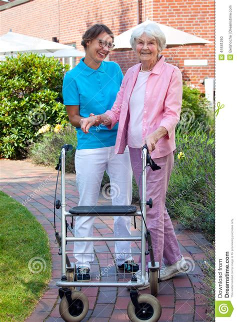 care assistant helping an elderly stock photo image