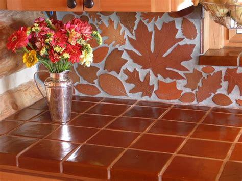 terracotta leaf backsplash and terracotta tile countertop