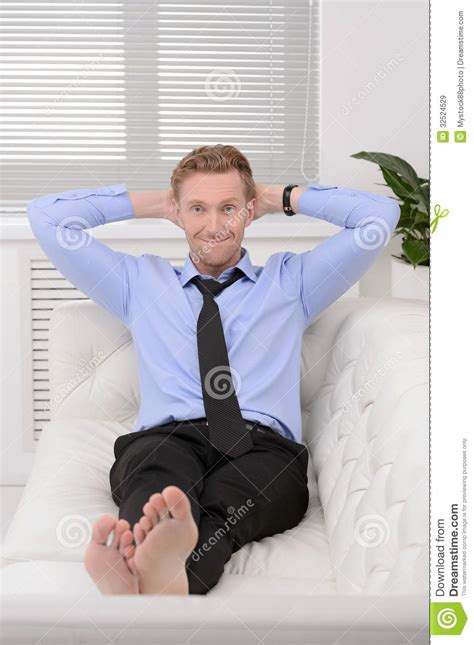 relaxing on the couch relaxing after working day cheerful young businessman