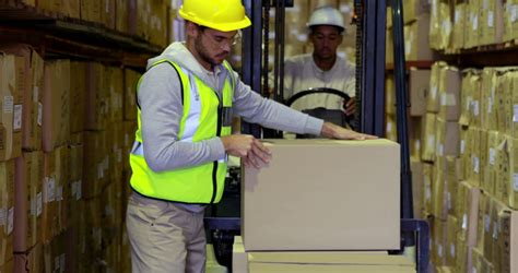 warehouse worker packing boxes on forklift in a large