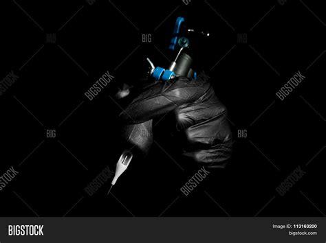 tattoo machine photography tattoo artist holding tattoo machine on black background