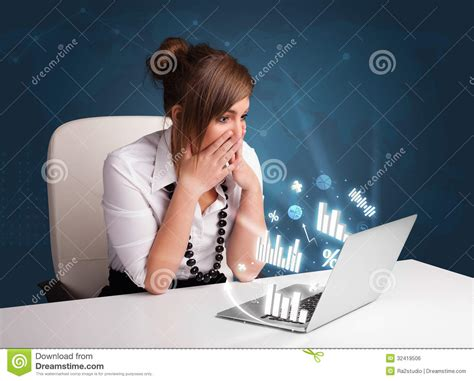 pretty sitting at desk and typing on laptop with