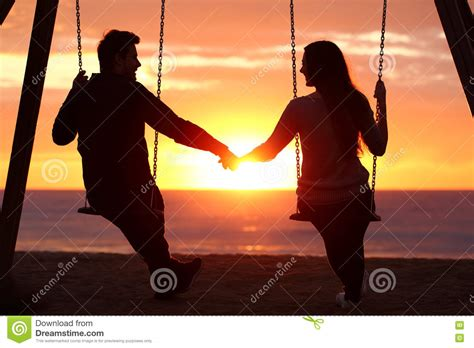 couple swing couple silhouette holding hands watching a sunrise stock