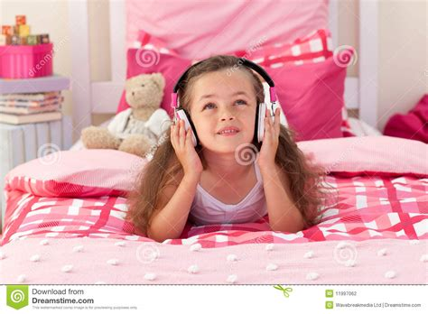 girl in bedroom cute girl listening music in the bedroom stock photo