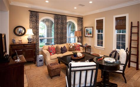 Elegant wicker ottoman in living room eclectic with dark wood furniture next to navy curtains