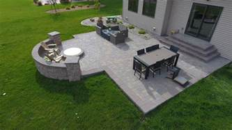 Backyard fire pit with seat wall and paver patio oasis