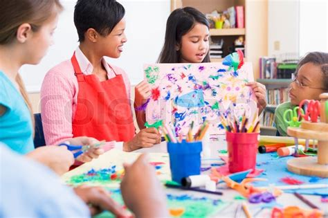 craft class for elementary school pupil in class showing picture to